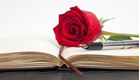 red rose on an open notebook lying on a wooden table Copyright: denis83 / 123RF Stock Photo